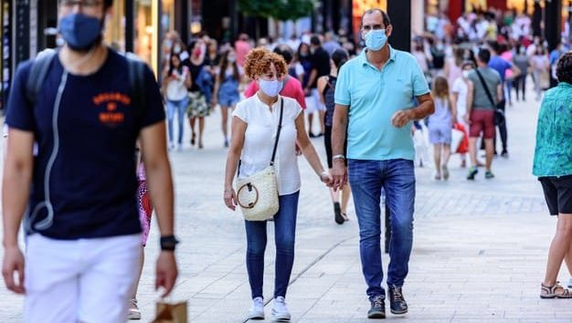 People with masks on walking in commercial street